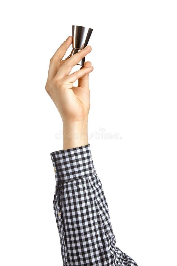 Conceptueel beeld van de barman De hand houdt een jigger op een witte achtergrond wordt geïsoleerd die stock afbeeldingen