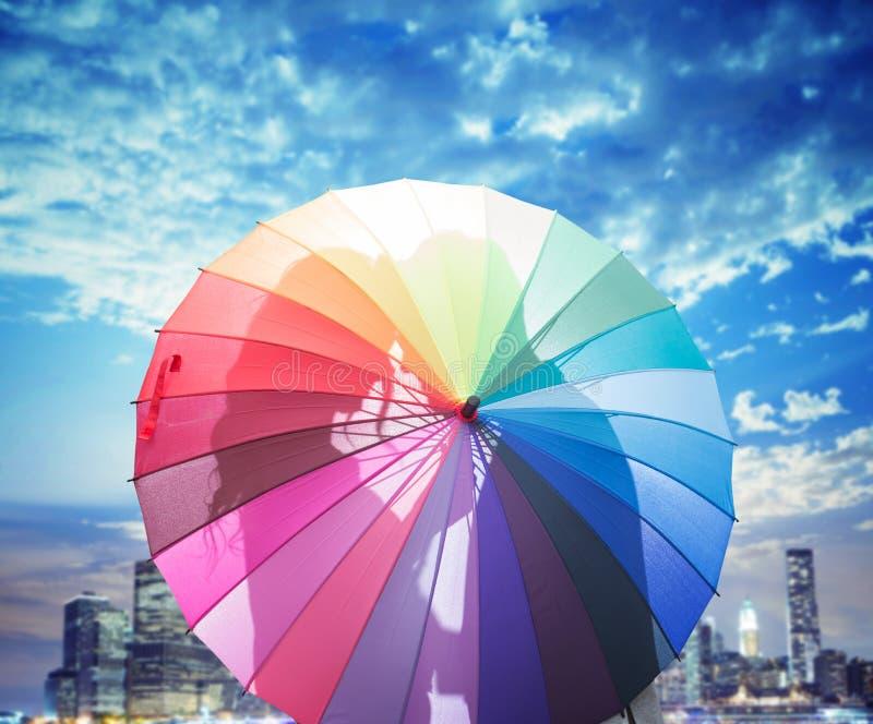 Conceptueel beeld van een paar die achter een paraplu kussen stock afbeelding