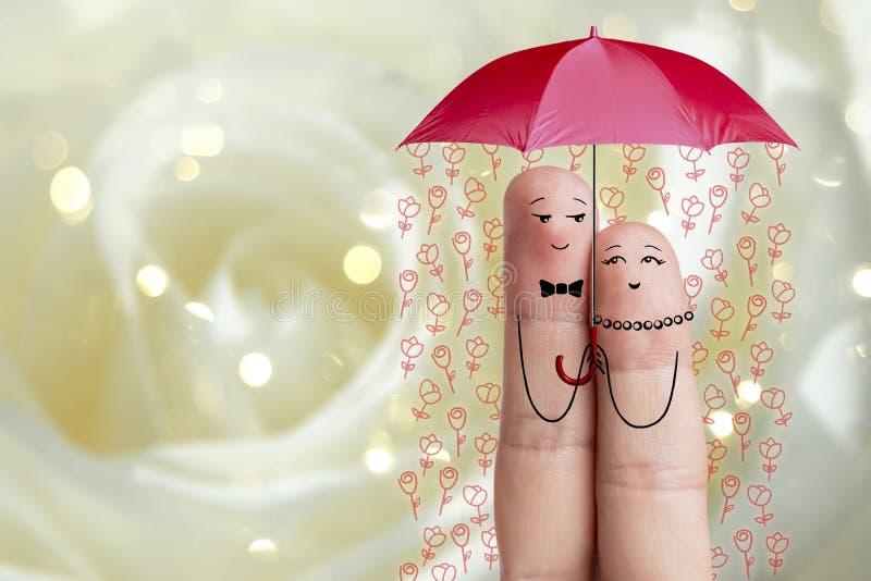 Conceptueel vingerart. De minnaars omhelzen en houden paraplu met dalende bloemen Het beeld van de voorraad stock fotografie
