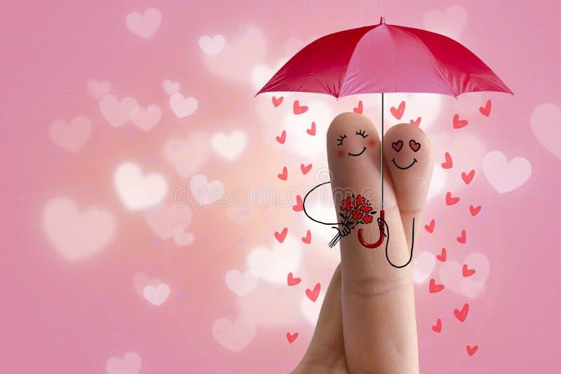 Conceptueel vingerart. De minnaars omhelzen en houden paraplu met dalende harten Het beeld van de voorraad stock fotografie