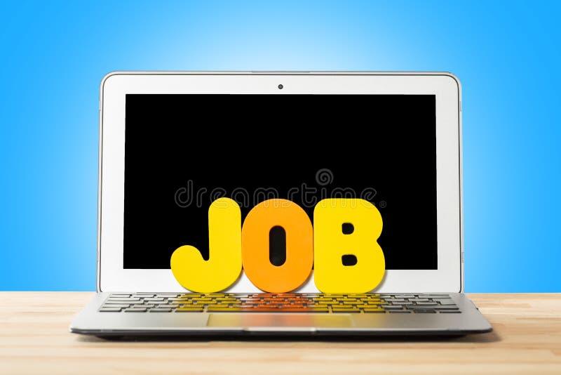 Conceptueel werkruimte of bedrijfsconcept Laptop computer met woordbaan van kleurrijke brieven tegen blauwe achtergrond stock afbeelding