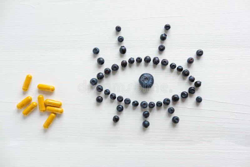 Conceptuele foto van de behandeling van visie Producten die visie verbeteren Bosbessen en vitaminen voor ooggezondheid Mening van stock afbeeldingen