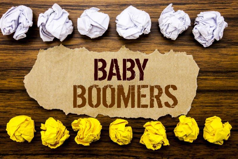 Conceptuele het woordbaby Boomers van de handtekst Bedrijfsconcept voor Demografische die Generatie op kleverige nota, houten met stock afbeelding