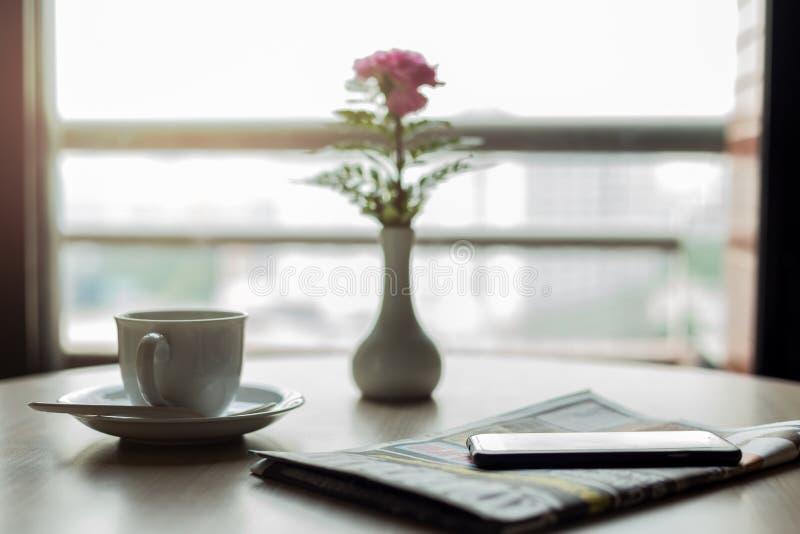 Conceptuele kop van koffie met krant en celtelefoon op houten stock afbeelding