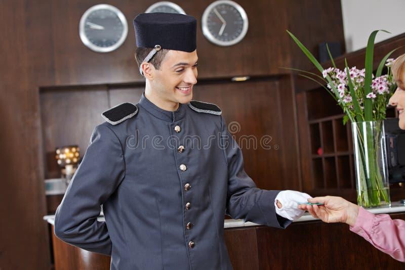 Concergie no hotel que dá o cartão chave à mulher fotos de stock