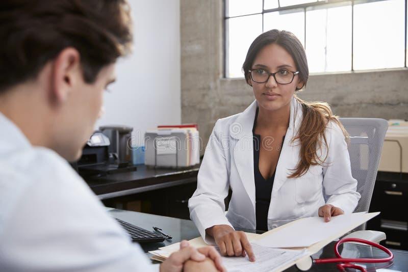 Concerned женский терапевт консультируя молодой мужской пациент стоковые фотографии rf