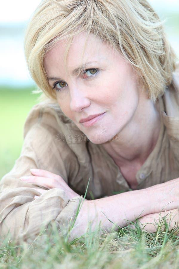Concerned женщина лежа на траве стоковые фотографии rf