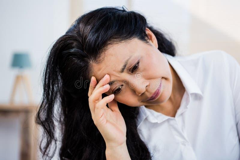 Concerned женщина сидя дома стоковые фотографии rf