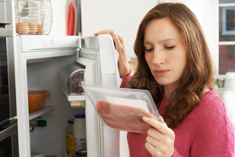 Concerned женщина смотря Pre упакованное мясо стоковая фотография