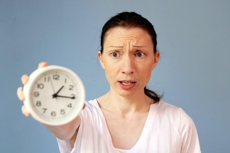 Concerned женщина указывая на контроль времени часов стоковые фото