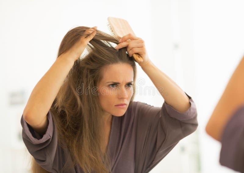 Concerned молодая женщина расчесывая волосы в ванной комнате стоковое изображение rf