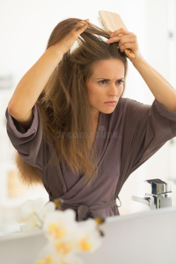 Concerned молодая женщина расчесывая волосы в ванной комнате стоковая фотография rf