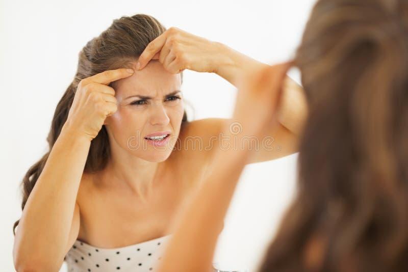 Concerned молодая женщина сжимая угорь в ванной комнате стоковая фотография