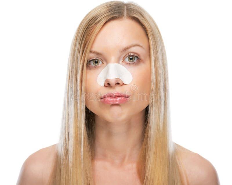 Concerned молодая женщина с ясными-вверх прокладками на носе стоковая фотография