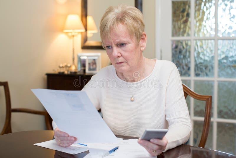Concerned старшая женщина рассматривая отечественные финансы стоковые фото