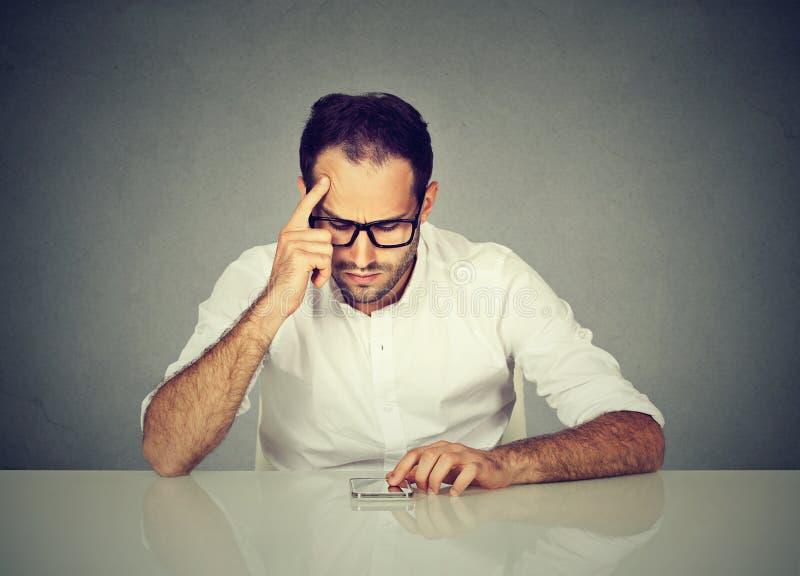 Concerned человек с телефоном на таблице стоковая фотография rf