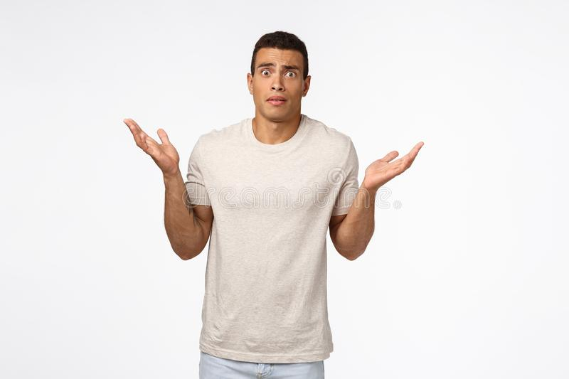 Concerned and alarmed tanned muscline young man standing shocked and confused, shrugging with hands spread sideways. Stare camera anxious and indecisive, have stock photos