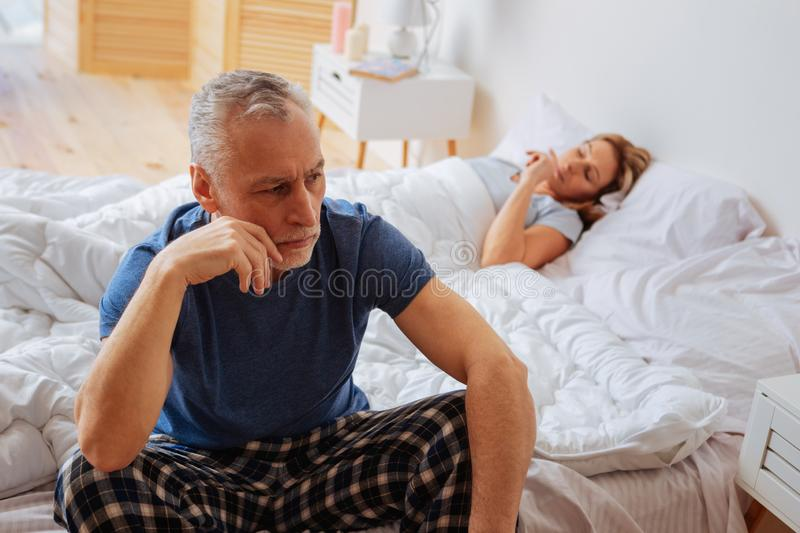 Concerned angry husband sitting on bed near sleeping wife. Angry husband. Concerned angry husband sitting on bed near sleeping wife after their argument royalty free stock images