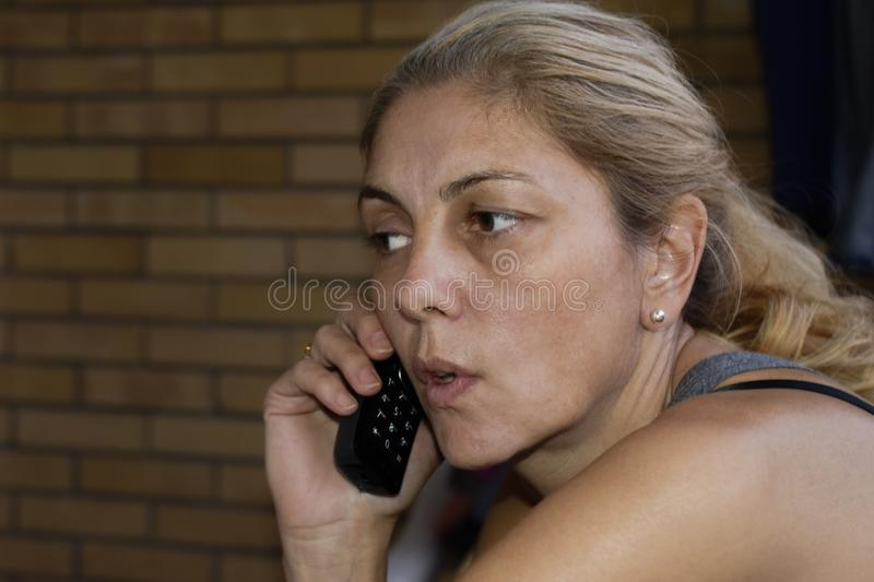 Concerned blonde woman on mobile phone royalty free stock image