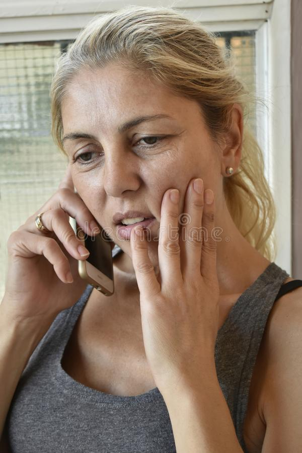 Concerned blonde woman on mobile phone royalty free stock photo