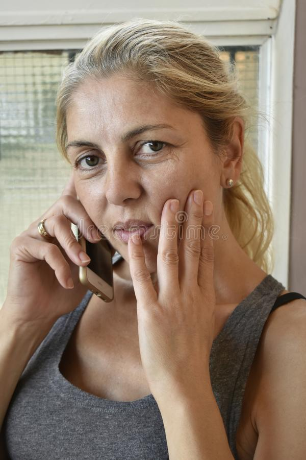 Concerned blonde woman on mobile phone stock photography