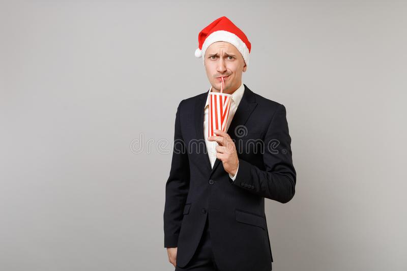Concerned business man in Christmas hat drinking cola or soda from plastic cup isolated on grey background. Achievement. Career wealth business. Happy New Year royalty free stock photo
