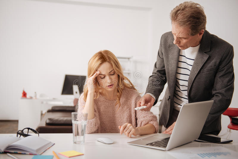Concerned businessman offering help to ill coworker in the office. What is wrong with you. Concerned mature skilled businessman standing in the business center royalty free stock photos