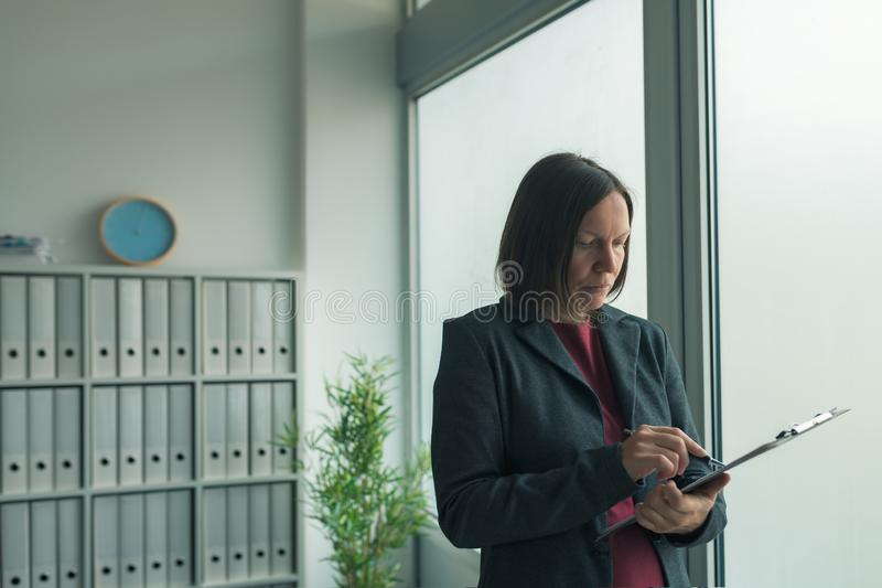 Concerned businesswoman reading business report papers in office stock photo