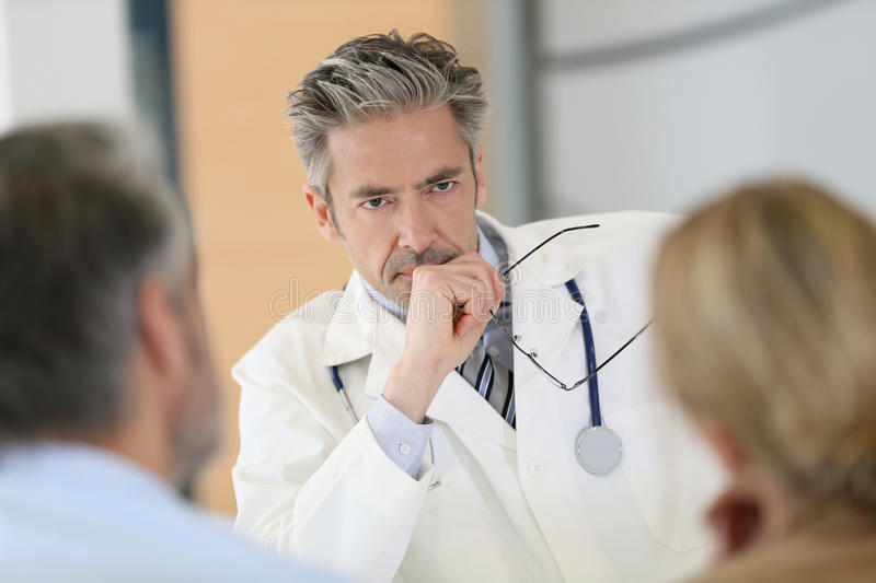 Concerned doctor meeting couple at hospital stock images
