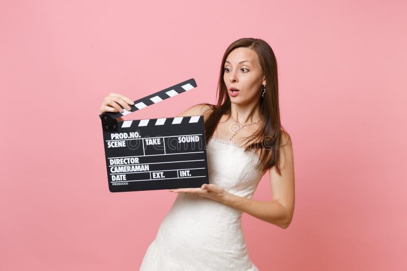 Concerned entsetzte Brautfrau im weißen Heiratskleid, das klassisches schwarzes Filmherstellung clapperboard auf Pastell hält stockfotos
