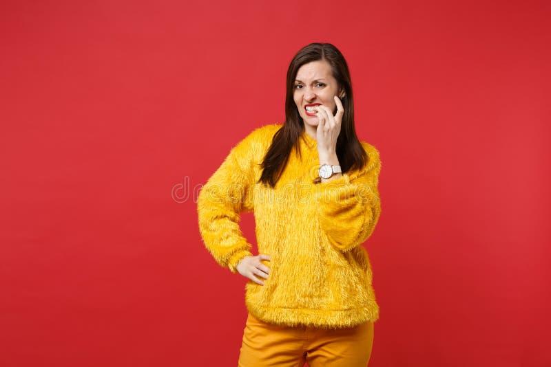 Concerned förbryllade den bekymrade unga kvinnan i gult pälströjaanseende, och gnaga spikar isolerat på den ljusa röda väggen arkivbild
