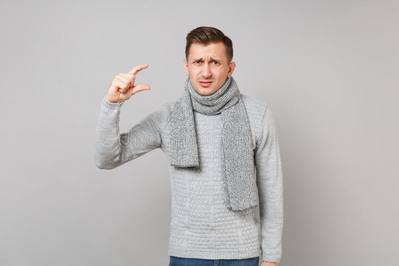 Concerned man in gray sweater, scarf gesturing demonstrating size with workspace on grey wall background. Healthy lifestyle, people sincere emotions, cold stock photography
