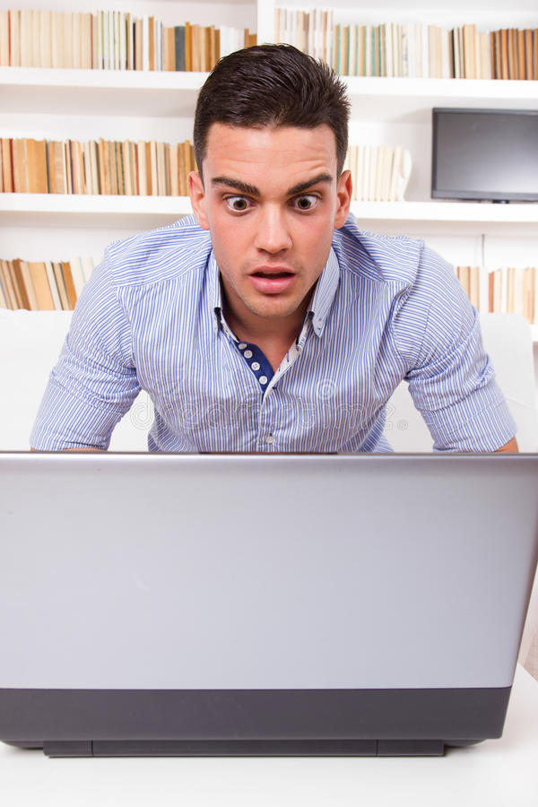 Concerned man looking at computer monitor shocked royalty free stock images