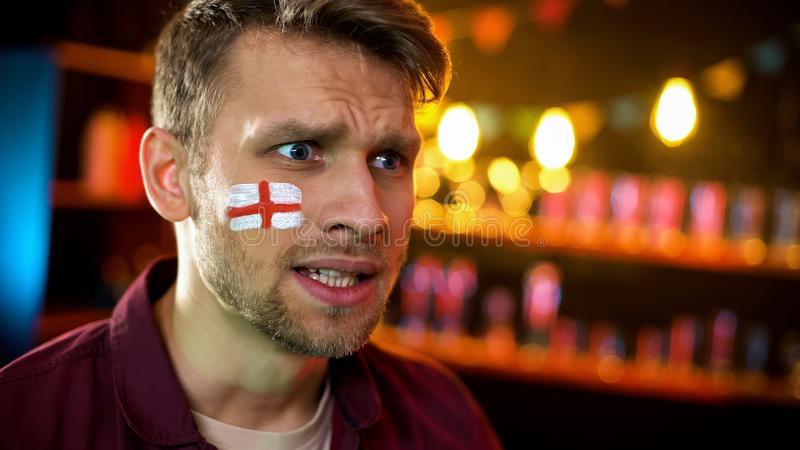 Concerned man with painted flag of england on cheek watching elections info. Stock photo royalty free stock photography