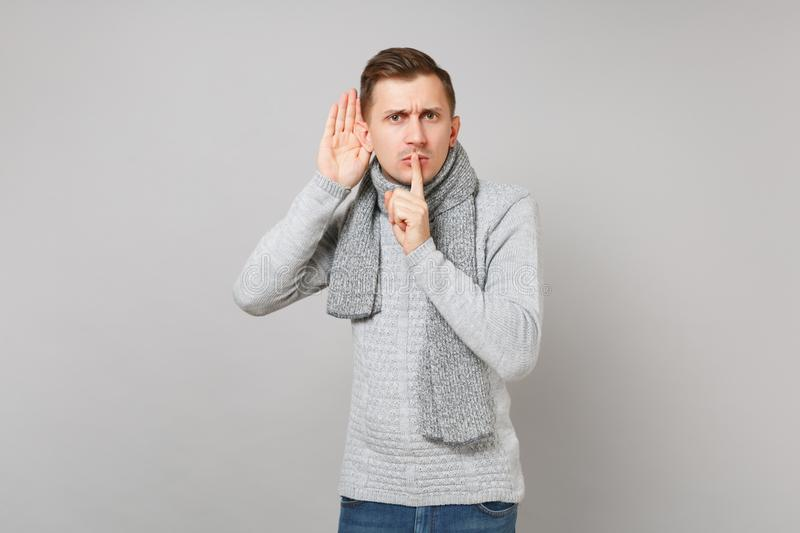 Concerned man in sweater, scarf say hush be quiet with finger on lips shhh gesture eavesdrop hearing on grey. Background. Healthy fashion lifestyle people stock photos