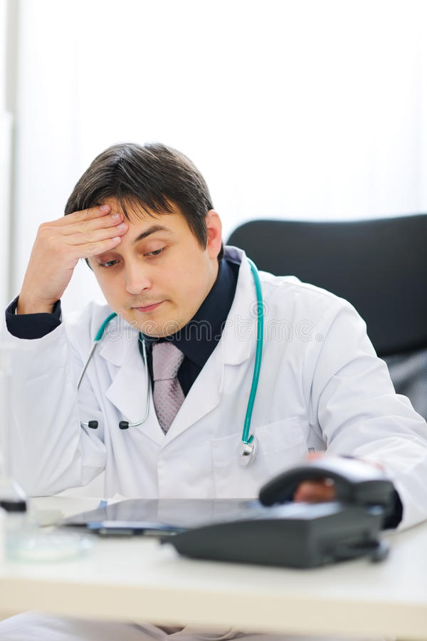 Concerned medical doctor picking up phone. Concerned modern medical doctor picking up phone royalty free stock photo