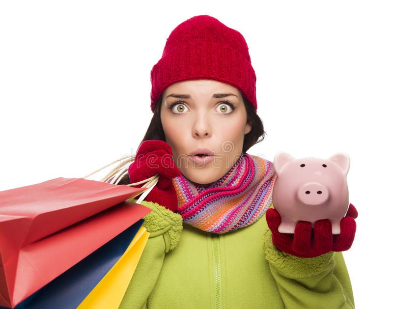 Concerned Mixed Race Woman Holding Shopping Bags and Piggybank. Concerned Mixed Race Woman Wearing Winter Clothes Holding Shopping Bags and Piggybank Isolated on stock image