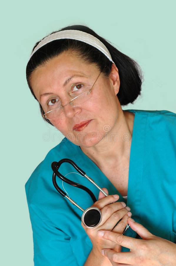 Concerned nurse. Older, attractive nurse ready to administer a physical exam stock photography