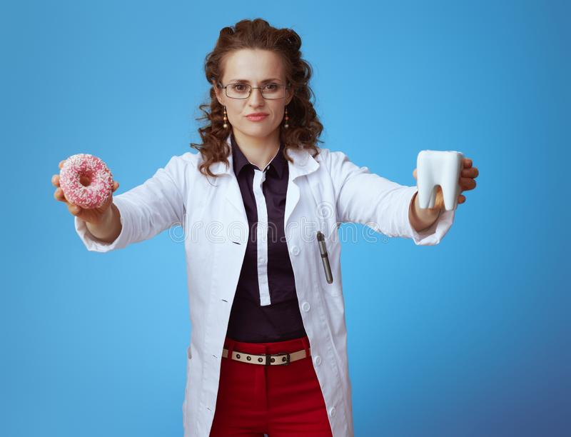 Concerned physician woman showing donut and white tooth on blue. Concerned elegant physician woman in bue shirt, red pants and white medical robe showing donut stock photo