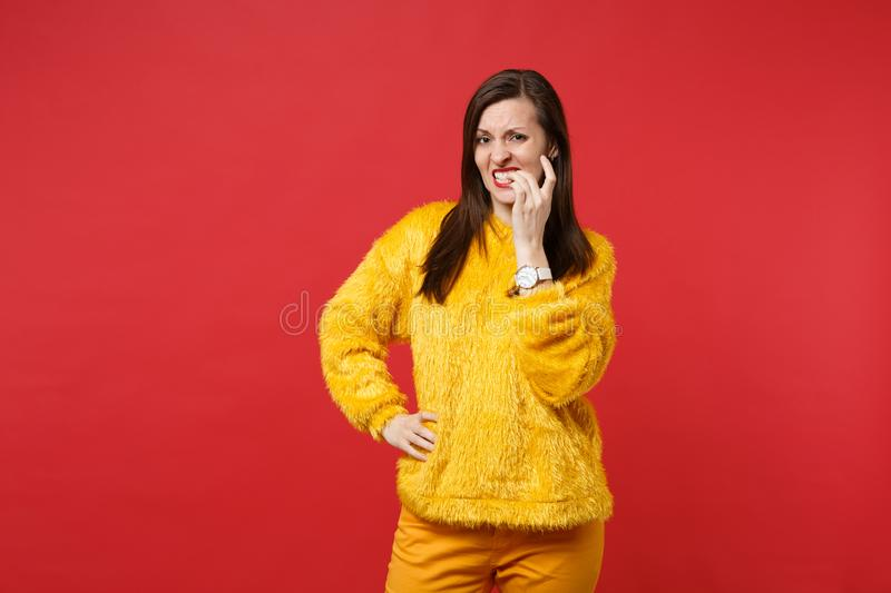 Concerned puzzled worried young woman in yellow fur sweater standing and gnawing nails isolated on bright red wall. Background in studio. People sincere stock photography