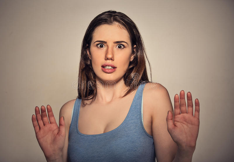 Concerned scared woman dodging something arms raised. Trying to avoid unpleasant situation isolated on gray wall background royalty free stock photos