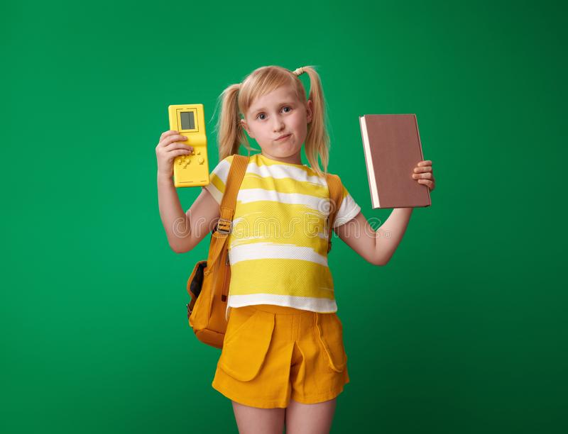 Concerned school girl holding book and video game stock photo