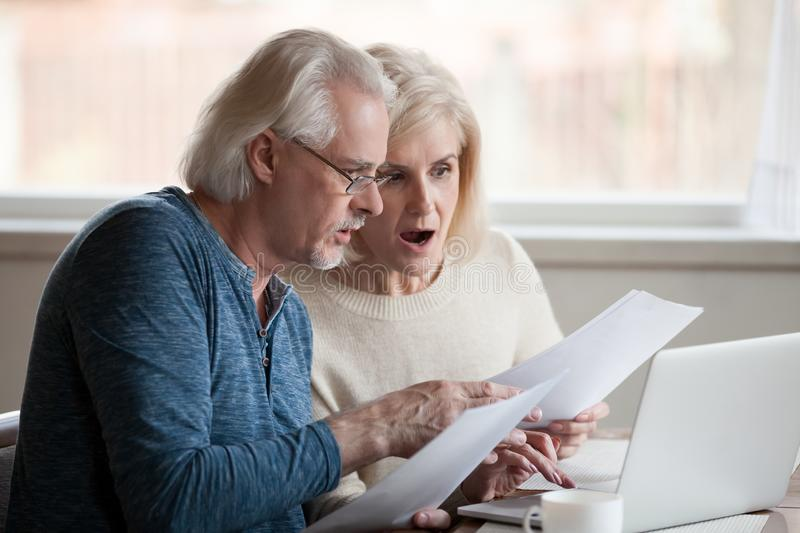 Concerned aged couple shocked by information online royalty free stock photos
