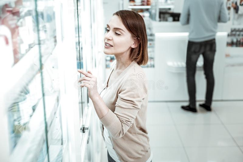 A concerned wife pointing at the vitamins in the pharmacy. A wife in a pharmacy. A concerned elegant wife pointing at the vitamins in the pharmacy with husband royalty free stock image