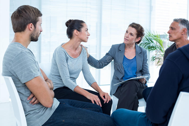 Concerned woman comforting another in rehab group. Concerned women comforting another in rehab group at a therapy session royalty free stock photo