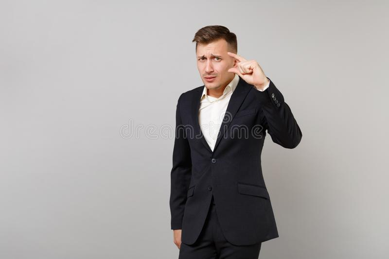 Concerned young business man in classic black suit, shirt gesturing demonstrating size with copy space isolated on grey. Wall background. Achievement career royalty free stock photography