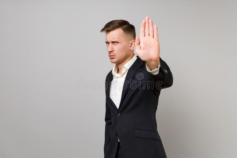 Concerned young business man in classic black suit and shirt showing stop gesture with palm isolated on grey wall royalty free stock images
