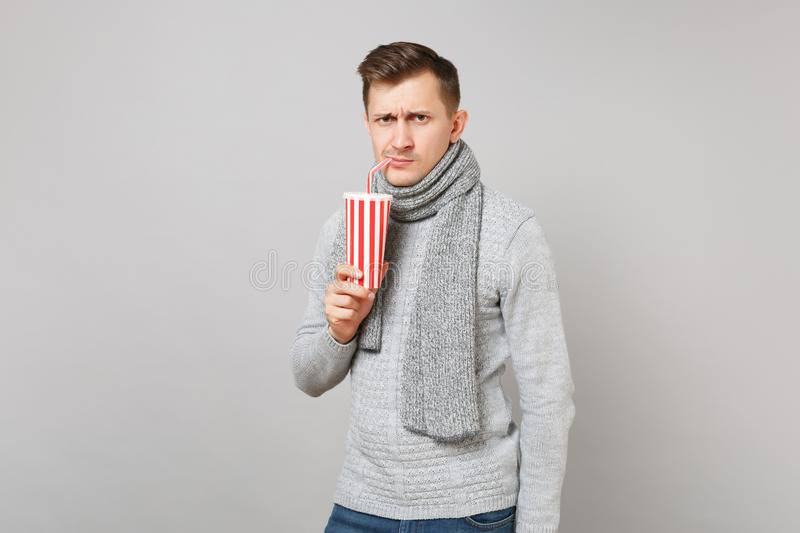 Concerned young man in gray sweater scarf drinking cola or soda from plastic cup isolated on grey background. Healthy. Fashion lifestyle people sincere emotions royalty free stock image
