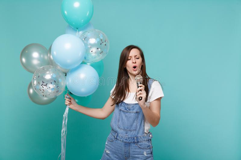 Concerned young woman in denim clothes sing song in microphone, celebrating, holding colorful air balloons isolated on. Blue turquoise wall background. Birthday stock image
