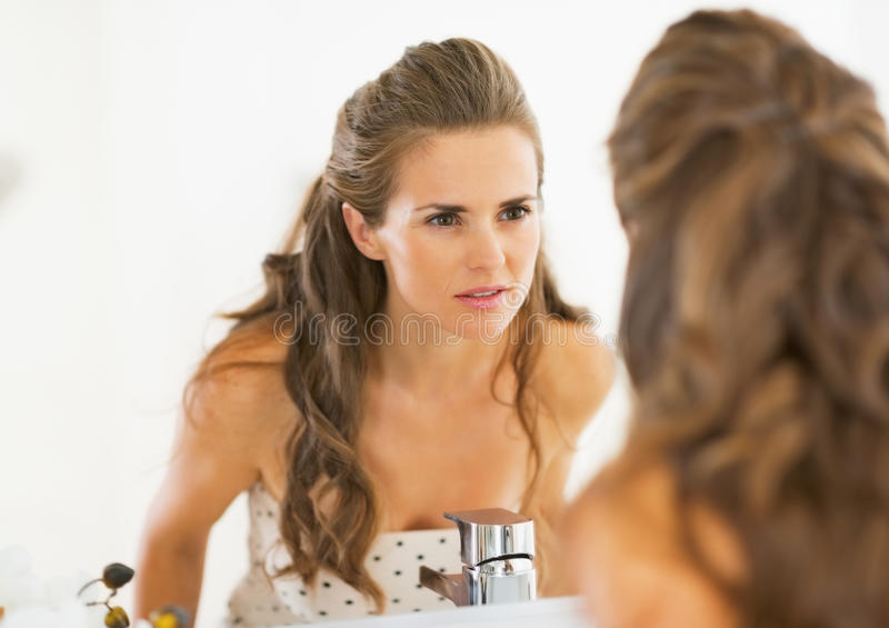 Concerned young woman looking in mirror stock photos